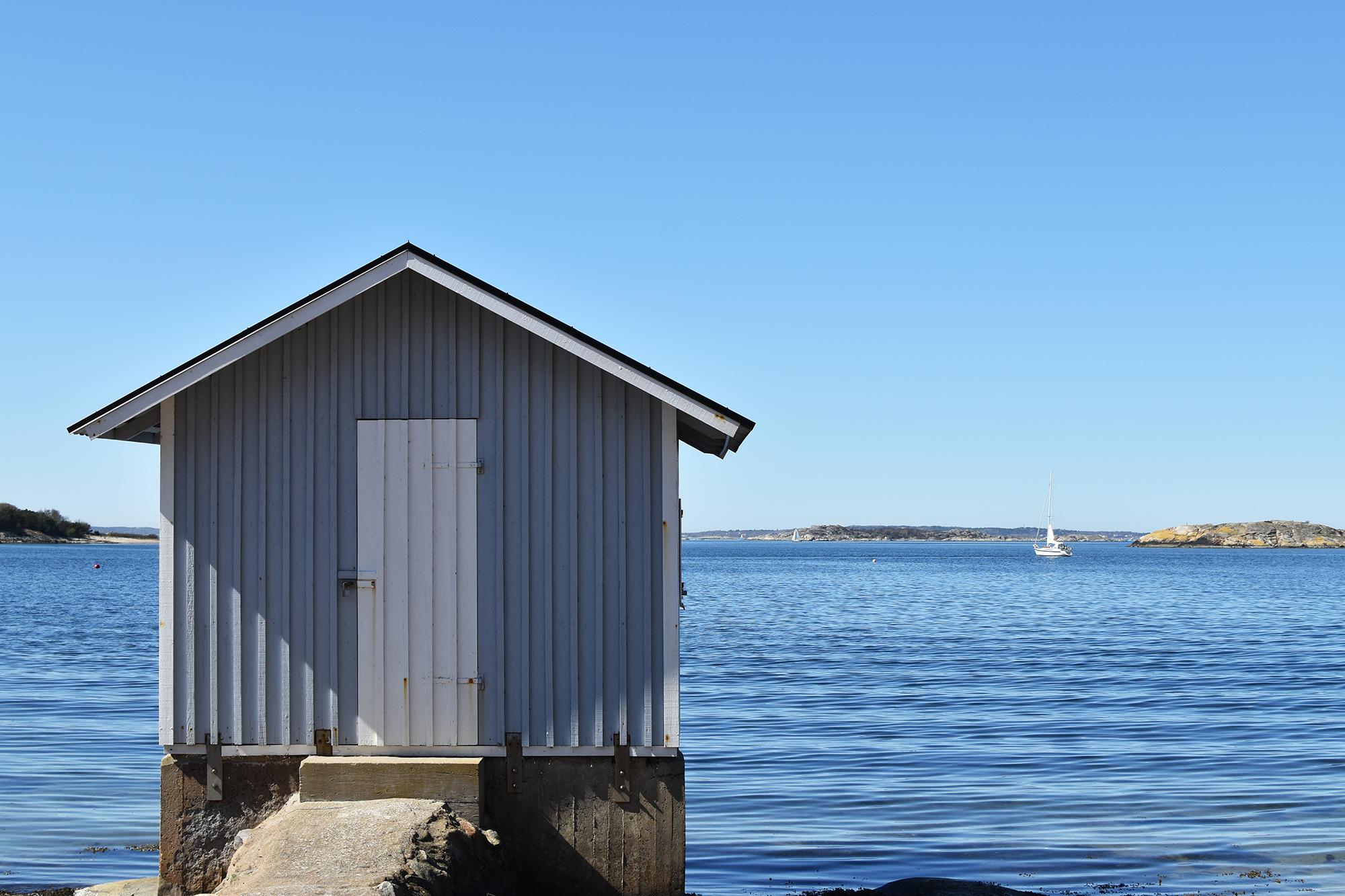 En sjöbod vid havet, med en segelbåt i bakgrunden och klarblått vatten i Göteborgs södra skärgård, söder om Göteborg city cirka en kilometer från bostäder och handel i Nya Hovås.